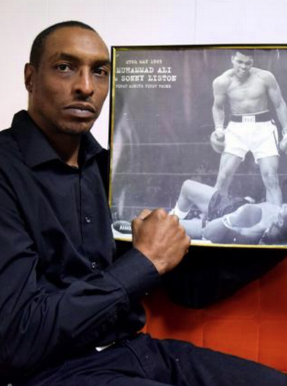 ali-junior-hlding-framed-photo-of-his-dad-287x386